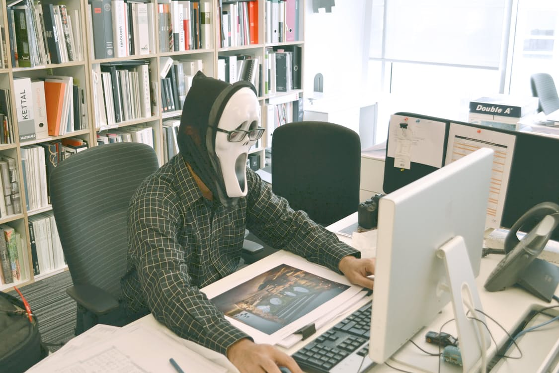 man in scream mask in front of a computer